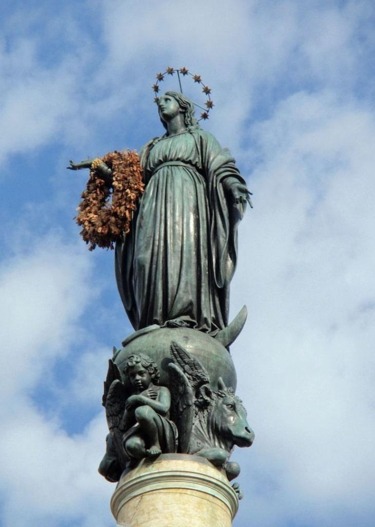 La statue de la Vierge Marie de la Place d'Espagne avec une couronne de fleurs autour de son bras.