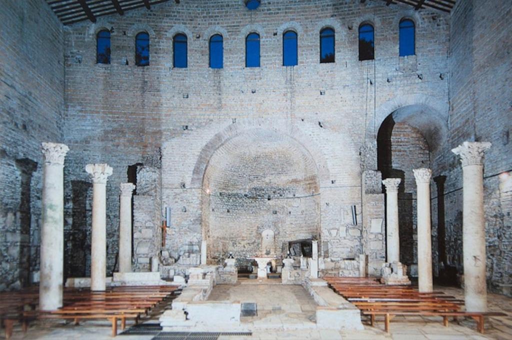 Intérieur des catacombes de Domitilla. 6 pilliers de chaque côté avec des bancs d'église.