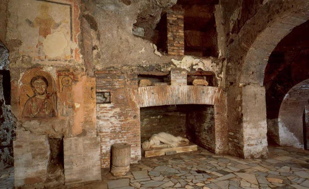 Intérieur des catacombes de Saint Calixte. On voit plusieurs niches creusées avec une statue allongée dans l'une d'elle.