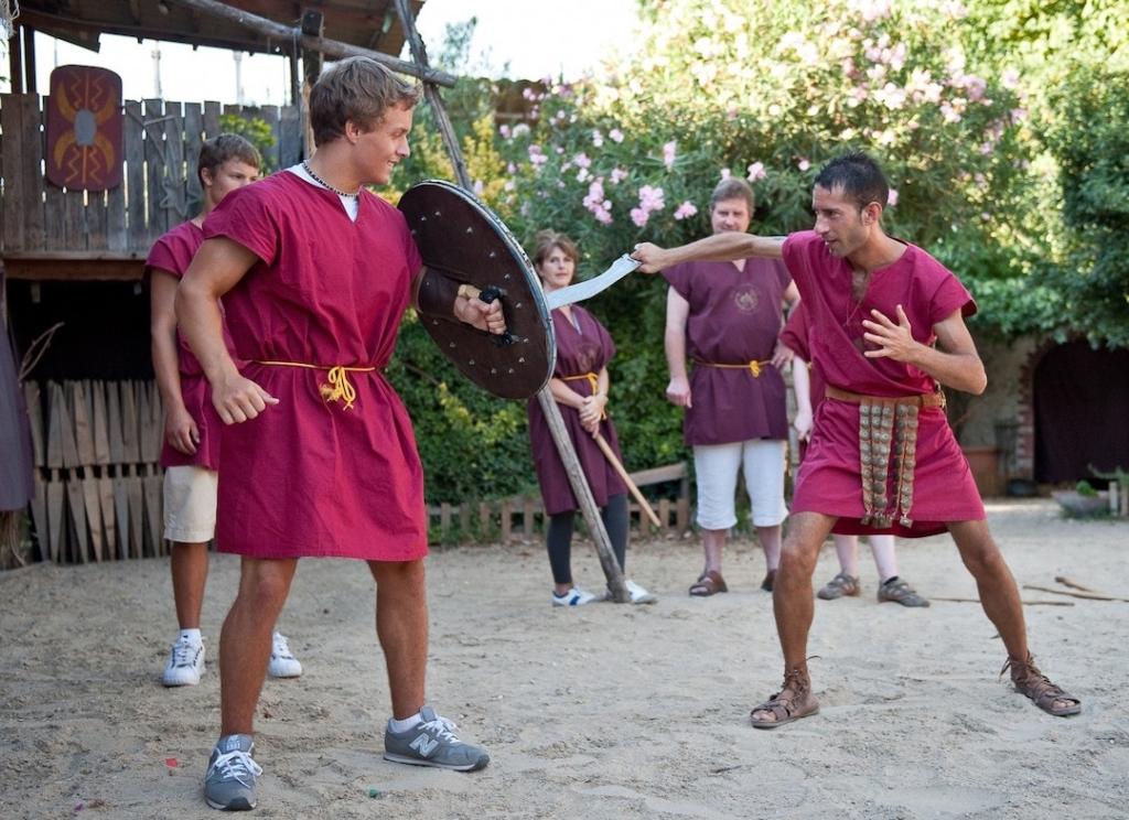 Deux personnes déguisées en gladiateurs en train de s'entraîner à combattre