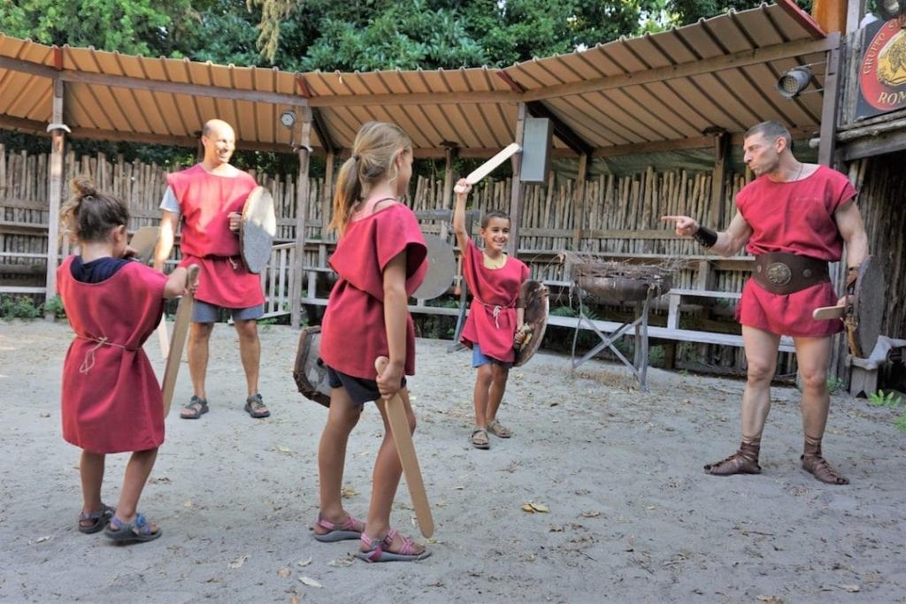 5 personnes habillées en tenue de gladiateurs en train de jouer aux gladiateurs dans une petite arène