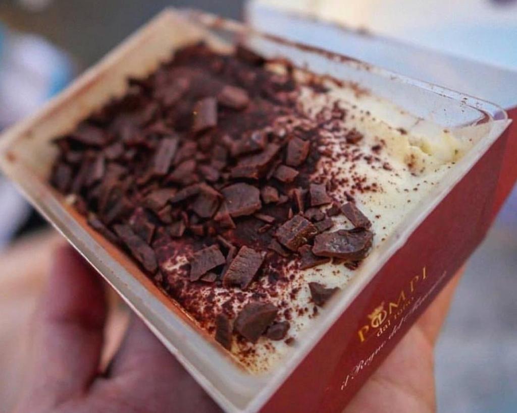 Portion de tiramisu dans une boîte en carton Pompi avec des éclats de chocolat sur le dessus