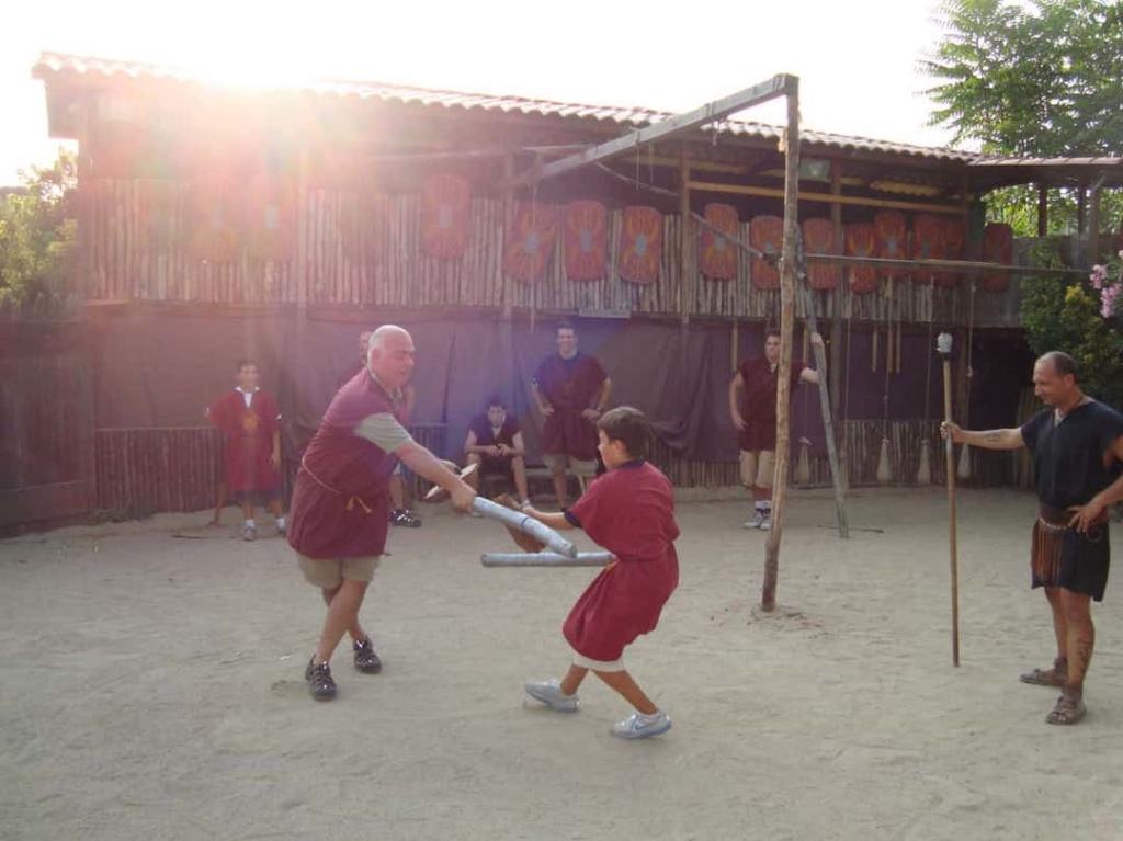 Un homme et un garçon habillés en gladiateurs en train de se battre à l'école des gladiateurs